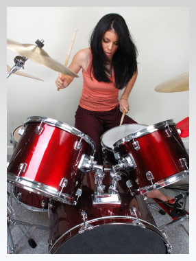 girl playing drums in bedroom